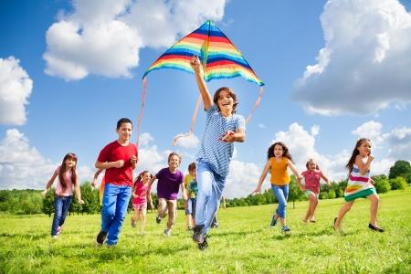 Feliz grupo de chicos y chicas niños con la cometa y riendo niño corriendo en el primer plano