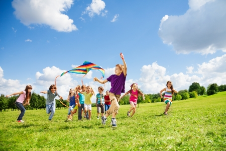Kids jongens en meisjes met vlieger draaien in een grote groep samen in het park op de zomerdag met enkele wolken in de blauwe hemel Stockfoto