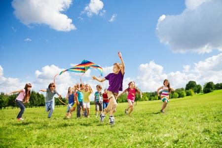 papalote: Ni�os ni�os y ni�as con cometa se ejecutan en un grupo grande juntos en el parque el d�a de verano con algunas nubes en el cielo azul