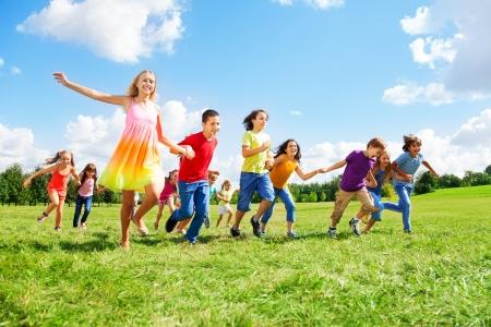 子供、男の子と女の子笑顔とカジュアルな服装で日当たりの良い夏の日、公園で走っているの大規模なグループ
