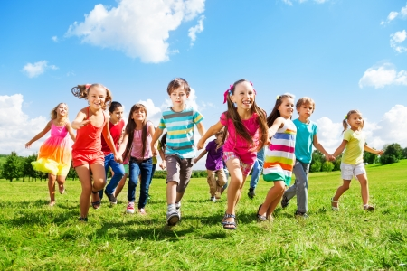 niño corriendo: Muchos niños diferentes, niños y niñas que se ejecutan en el parque en día soleado de verano en ropa casual Foto de archivo