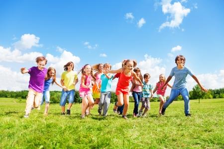 캐주얼 옷 화창한 여름 날에 공원에서 실행하는 아이, 친구의 남자와 여자의 큰 그룹