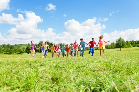 Large group of happy smiling kids, boys and girls running in the park on sunny summer day in casual clothes Imagens