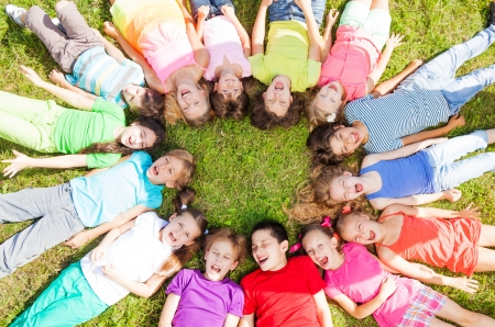 female kid: 14 kids laying in a circle in the grass with happy faces shoot from above