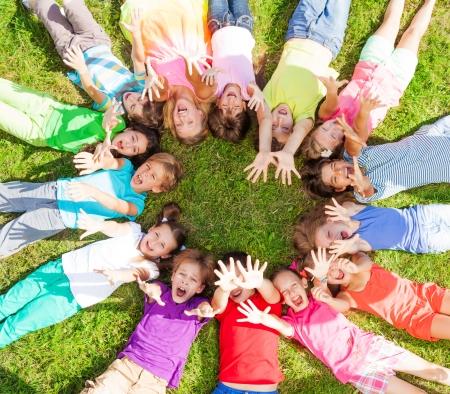 niÑos contentos: 14 niños que ponen en un círculo en la hierba con las caras felices disparan desde arriba levantar las manos por encima de Foto de archivo