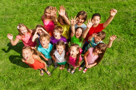 large group: Large group of happy kids, boys and girls, about 10 years old standing on the green grass top view Stock Photo