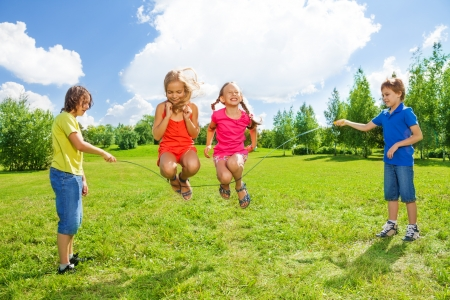 skip: Two girls jumping over the rope with boys rotating the rope Stock Photo