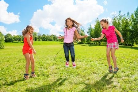 3 人の女の子、公園でロープを飛び越えてアクティブ ゲーム外で楽しんでいます。