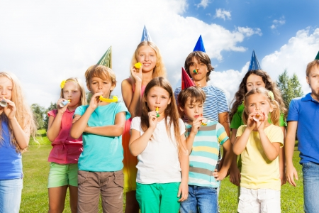 age 5: Large group of kids age 5 to 11 outside on a birthday party blowing noisemakers horns and twisted whistles
