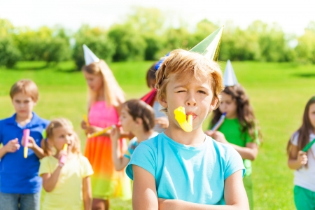 One little boy blow noisemaker on a birthday party wearing cap with friends standing on background photo