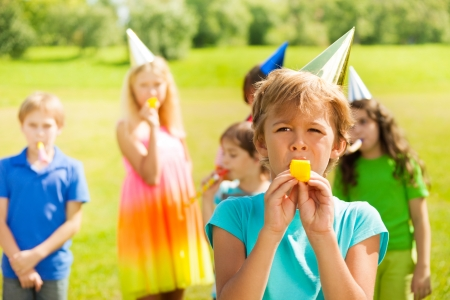 whistles: Handsome boy blowing twisted whistle in party horn with many kids on the background