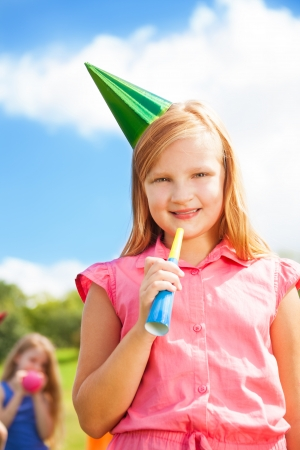 noisemaker: Portrait of a girl blows noisemaker horn on a birthday party wearing cap