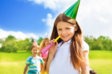 noisemaker: Little girl blow noisemaker on a birthday party wearing cap with friends standing on background