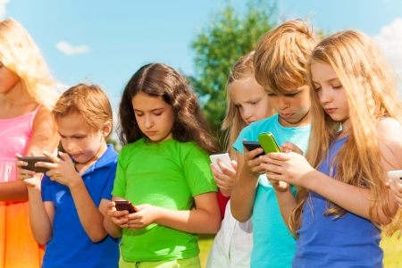 Group of busy kids looking at their phones texting sms and playing staying outside photo