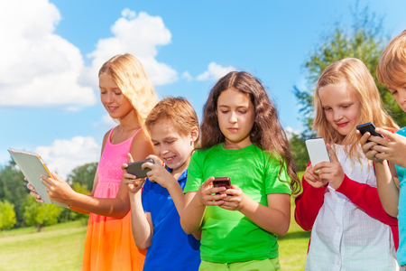 Five happy kids stnading with phones and digital devices photo