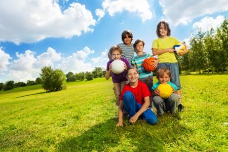 Groep zeer gelukkige zes jongens, team zittend op het gras met ballen en glimlachen, op zonnige zomerdag
