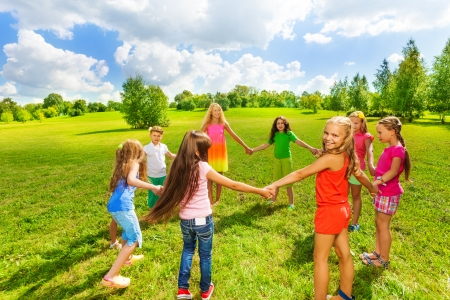 Large group of happy girls play roundelay and stand in circle in the park on the green field
