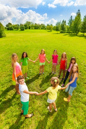 Large group of happy girls play roundelay and stand in circle in the park on the green grass on sunny summer day, view from above photo