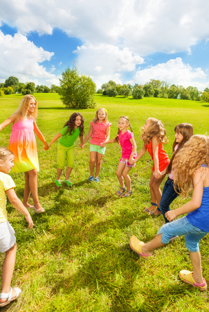 Large group of happy girls play roundelay and stand in circle in the park on the green grass on sunny summer day photo