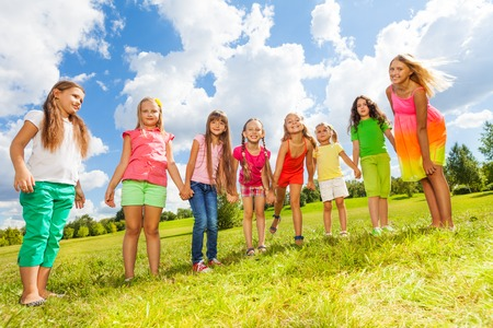 Large group of happy girls standing in a row in the park on the green grass on sunny summer day photo