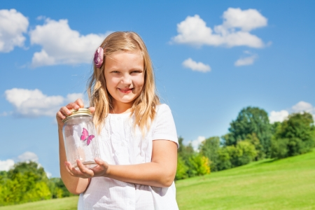 Litle blond girl with jar and red butterfly inside photo
