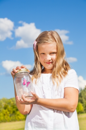 Litle blond girl with jar and red butterfly inside standing in the park on bright sunny day photo