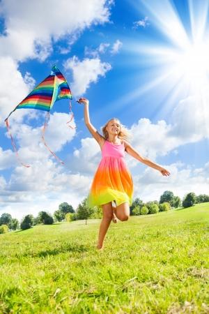 papalote: Niña feliz de 14 años corriendo en el campo con una gran cometa de color
