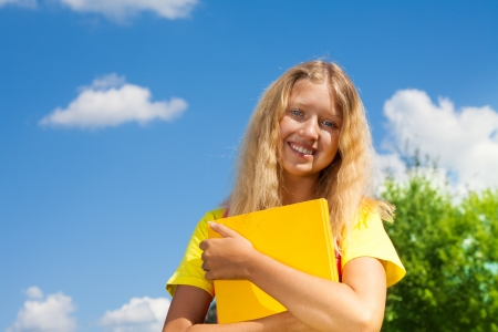 13: Happy blond 13 years old girl stand with with the yellow book in the park on bright sunny summer day. Stock Photo