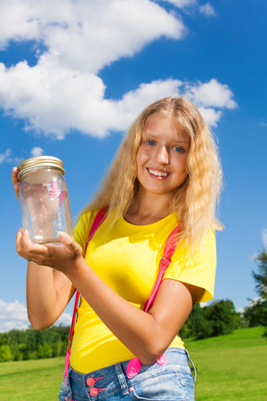 13: Happy 13 years old blond girl holding glass jar with butterfly, standing in the park on sunny summer day  Stock Photo