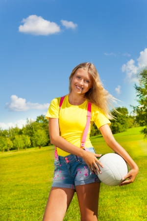 13: Happy and smiling 13 years old girl with long blond hair standing in the grass with the ball in the park on sunny summer day Stock Photo