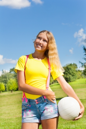 Happy and smiling 13 years old girl with long blond hair standing in the grass with the ball in the park on sunny summer day with blue sky and white clouds photo