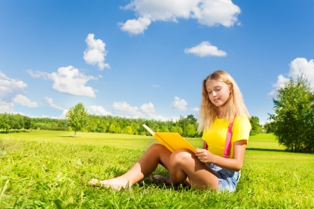 13: Happy blond girl with the yellow book in the park on bright sunny summer day. Stock Photo