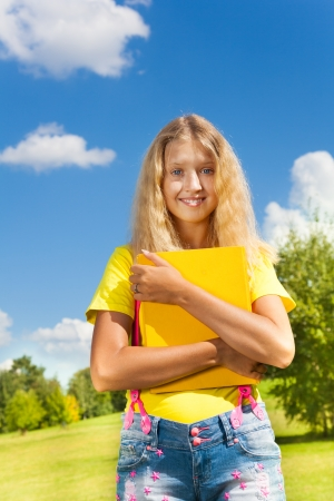 13: Blond smiling girl with the yellow book in the park on bright sunny summer day