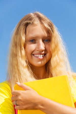 13: Close portrait of happy blond 13 years old girl stand with with the yellow book in the park on bright sunny summer day.