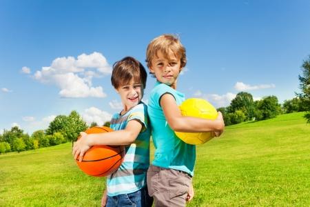 Dwaj bracia stoją z posiadania piłki stojących w parku w słoneczny letni dzień Zdjęcie Seryjne