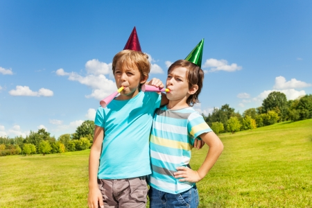 Portrait of two boys on birthday party having fun with blowing into noisemaker loudly  Stock Photo