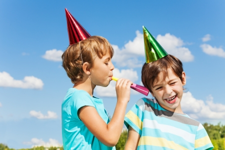 whistles: Two boys on birthday party having fun with blowing into noisemaker loudly