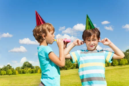 Two boys one with finger in his ears and the other blow loud in the years with nosemaker Stock Photo