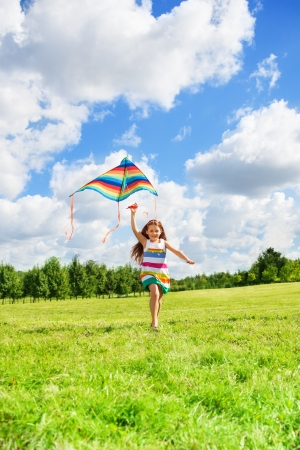 kites: Girl with kids running in the field on sunny summer day