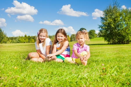 Three happy girls, sisters, sitting in the grass in park together photo