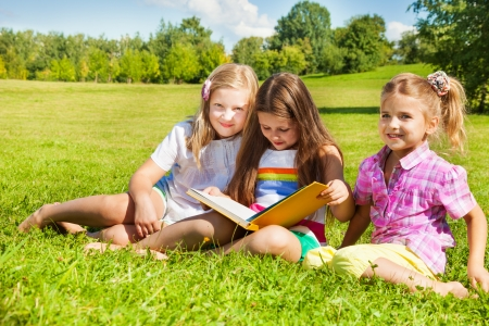 Three happy girls, sisters, sitting in the grass in park together and reading a big yellow book photo