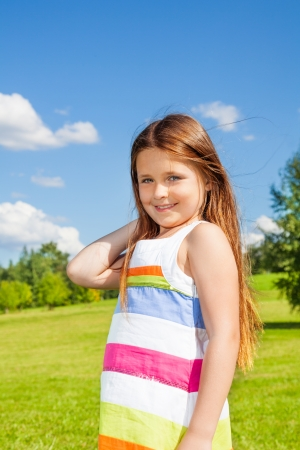 Beautiful portrait smiling little girl with long hairs standing outside on sunny day photo