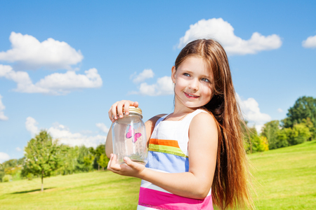 eight years old: Beautiful girl with long dark hair 8 years old hold jar with butterfly standing in the park on bright sunny summer day Stock Photo