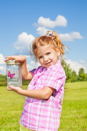 6 years: Little happy 6 years old girl standing in the park and holding jar with red butterfly very excited and happy Stock Photo