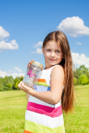 eight years old: Beautiful girl with long dark hair 8 years old hold jar with butterfly standing in the field on bright sunny summer day Stock Photo