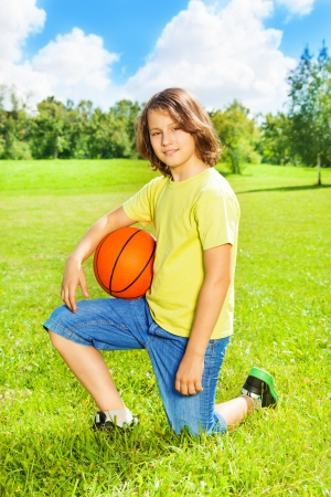 Portrait of 12 years old boy sit on squads with basketball ball on the field on bright sunny day