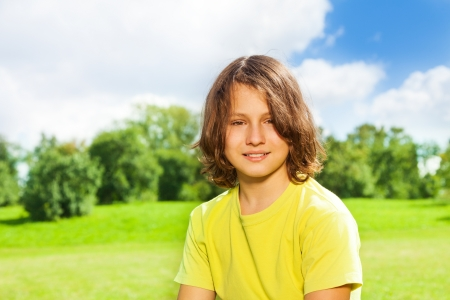 Nice handsome 12 years old boy portrait in the park outside on sunny day photo