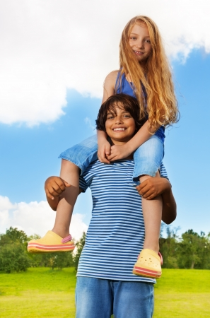 Two 10 years old kids, boy carry girl on his shoulders, both happy and smiling, in the park on sunny summer day photo