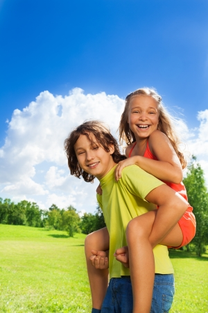 Two school age children boy carry girl on her back, both happy, smile, on sunny day photo