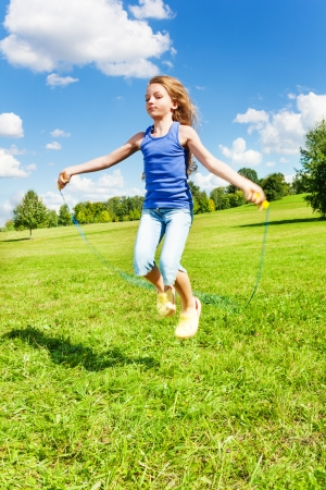 Beautiful girl with skipping rope jumping in the park on green grass field on sunny summer day photo